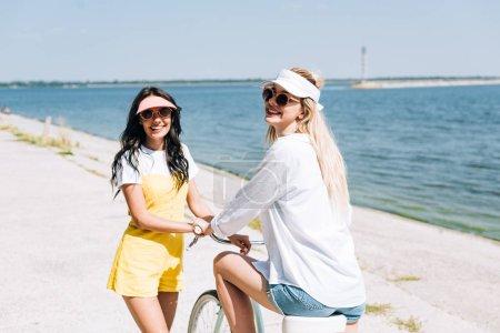 Photo pour Filles heureuses avec vélo près de la rivière en été - image libre de droit