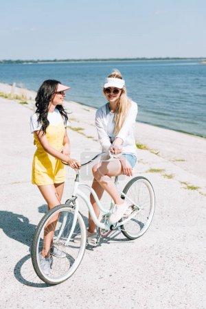 Lächelnde blonde und brünette Mädchen mit Fahrrad in Flussnähe im Sommer