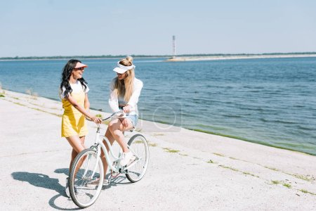 Photo for Cheerful blonde and brunette girls with bike near river in summer - Royalty Free Image