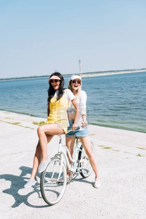Photo for Happy blonde and brunette girls with bike near river in summer - Royalty Free Image