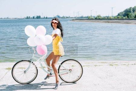 Photo pour Vue de côté de beau vélo d'équitation de fille de brunette avec des ballons près de la rivière - image libre de droit