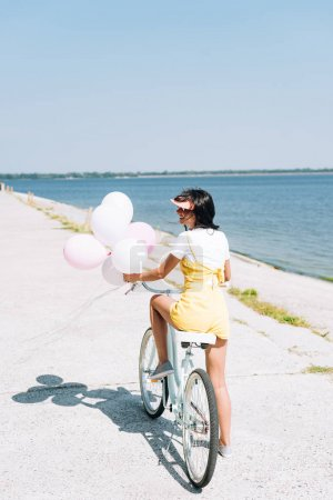 Photo for Back view of beautiful brunette girl riding bike with balloons near river - Royalty Free Image