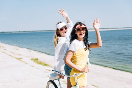 Photo for Blonde and brunette girls with bike waving hands near river in summer - Royalty Free Image