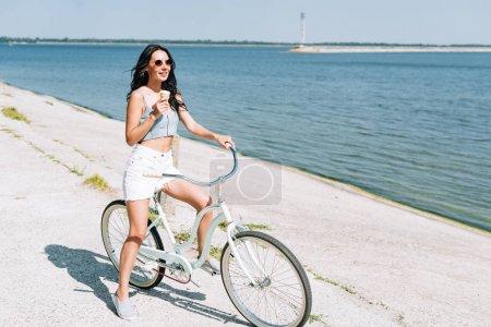 Photo pour Fille brune souriante avec crème glacée équitation vélo près de la rivière en été - image libre de droit