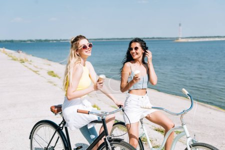 happy blonde and brunette girls riding bikes with ice cream near river in summer