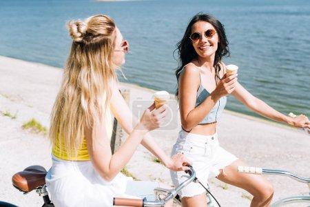 Lächelnde blonde und brünette Mädchen, die im Sommer Fahrräder mit Eis in Flussnähe fahren