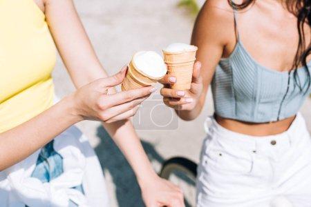 Photo pour Vue recadrée de filles à vélo avec de la crème glacée en été - image libre de droit