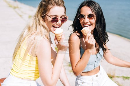 happy blonde and brunette girls eating ice cream