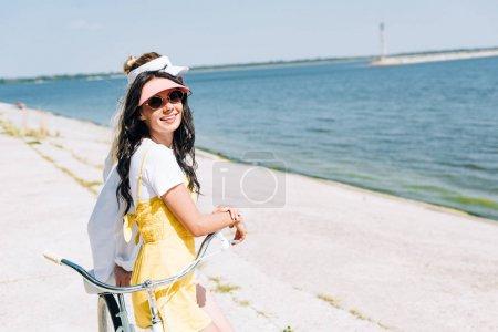 Photo pour Vue latérale des filles avec le vélo près de la rivière en été - image libre de droit