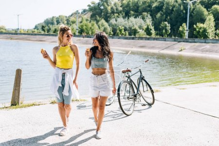 Photo pour Filles blondes et brunes souriantes près de vélos avec de la crème glacée à la rivière en été - image libre de droit