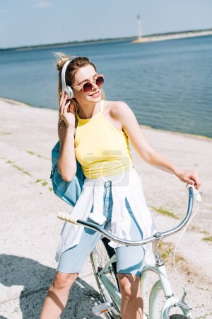 Photo for Blonde girl with backpack biking and listening music in headphones near river in summer - Royalty Free Image