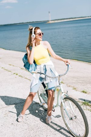 Photo for Blonde girl biking and listening music in headphones near river in summer - Royalty Free Image