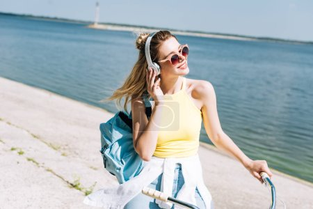 Photo for Happy girl with backpack biking and listening music in headphones near river in summer - Royalty Free Image