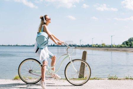 Photo pour Vue latérale de la fille avec le vélo de sac à dos et la musique d'écoute dans des écouteurs près de la rivière en été - image libre de droit