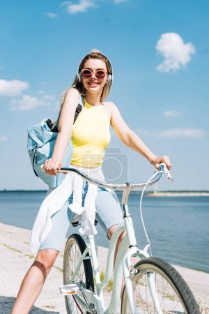 Photo for Girl with backpack biking and listening music in headphones near river - Royalty Free Image