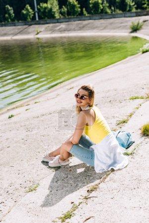 chica rubia feliz sentado cerca del río en verano
