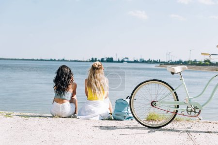 Photo for Back view of blonde and brunette friends sitting near bike and river in summer - Royalty Free Image