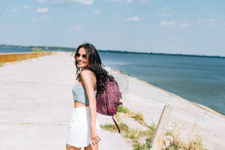 Foto de Chica morena feliz caminando con mochila cerca del río en verano - Imagen libre de derechos