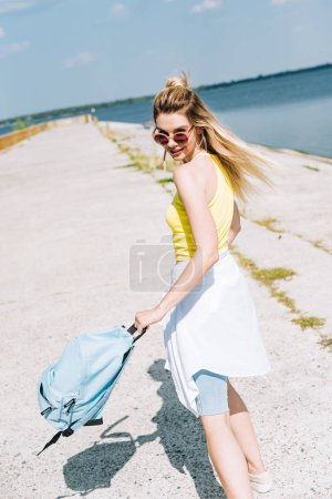 Photo for Blonde girl with backpack near river in summer - Royalty Free Image