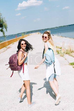 Foto de Chicas alegres caminando con mochilas cerca del río en verano - Imagen libre de derechos