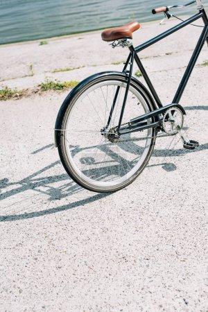 Photo pour Vélo sur l'asphalte près de la rivière bleue en été - image libre de droit