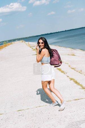 Foto de Chica morena feliz en gafas de sol caminando con mochila cerca del río en verano - Imagen libre de derechos