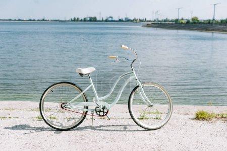 Photo pour Vue latérale de bicyclette près de la rivière bleue en été au soleil - image libre de droit