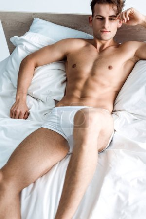 selective focus of handsome young man lying on bed