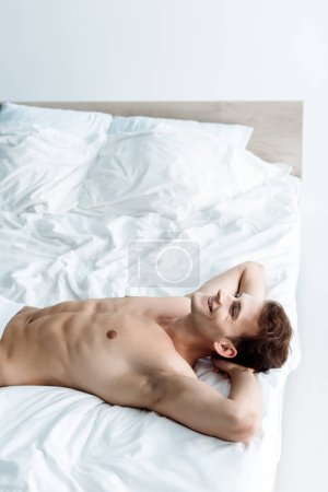 Photo for Sexy young man smiling while lying on bed - Royalty Free Image