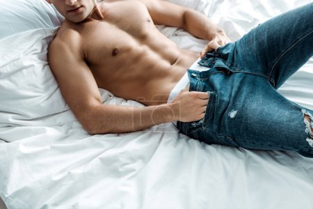 Photo for Cropped view of shirtless man taking off blue jeans while lying on bed - Royalty Free Image