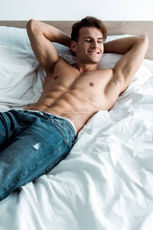 Photo for Cheerful man in denim jeans lying on bed at home - Royalty Free Image