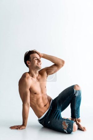 Photo for Cheerful and shirtless man touching hair and sitting on white - Royalty Free Image