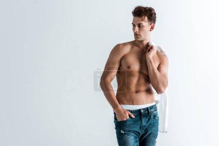 Photo pour Jeune homme musclé en jean denim debout avec la main dans la poche et tenant chemise isolée sur blanc - image libre de droit