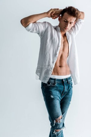 Photo for Sexy man in blue jeans and shirt standing isolated on white - Royalty Free Image