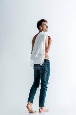 Photo pour Homme sexy dans la chemise de fixation de jeans de jeans et restant sur le blanc - image libre de droit