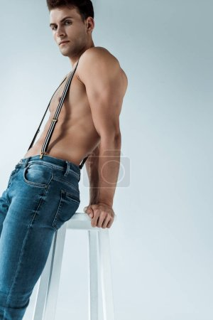 Photo for Handsome and sexy man sitting on chair on white - Royalty Free Image