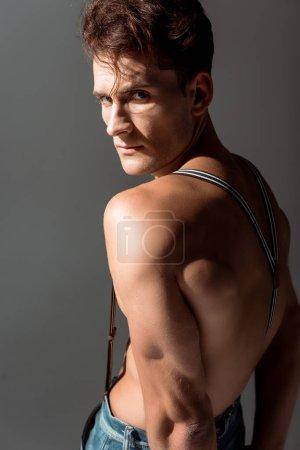 Photo pour Homme torse nu en jarretelles regardant la caméra isolée sur gris - image libre de droit