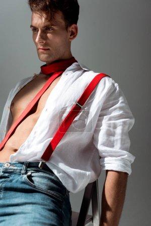 Foto de Joven guapo con camisa blanca sentado en la silla en gris - Imagen libre de derechos