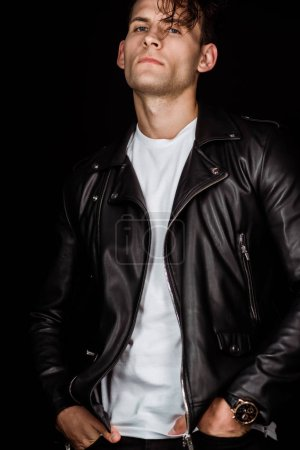 Photo for Stylish man in leather jacket standing with hands in pockets isolated on black - Royalty Free Image