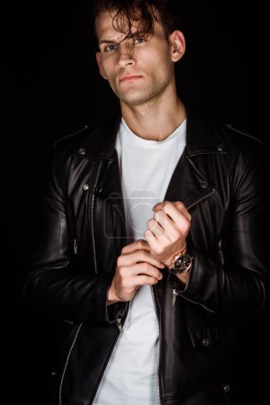 Photo pour Homme élégant en cuir veste toucher montre isolé sur noir - image libre de droit