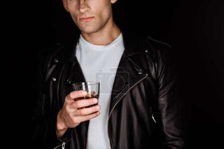 Photo for Cropped view of trendy man holding glass with whiskey isolated on black - Royalty Free Image