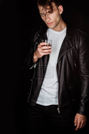 Photo for Trendy man holding glass with whiskey isolated on black - Royalty Free Image