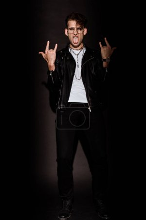 Photo for Trendy man in glasses showing rock sign while sticking out tongue on black - Royalty Free Image