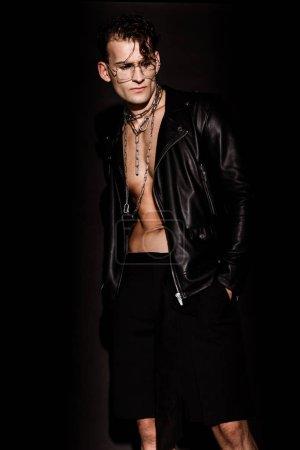 Photo pour Homme sexy dans des glaces et la veste en cuir restant avec des mains dans des poches sur le noir - image libre de droit