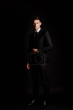 Photo for Handsome businessman in suit standing isolated on black - Royalty Free Image