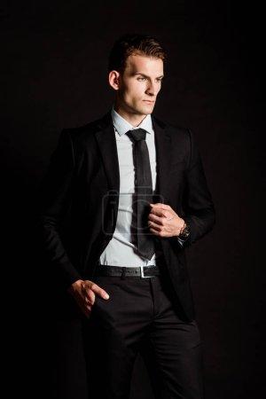 Photo pour Homme d'affaires beau dans l'usure formelle restant avec la main dans la poche d'isolement sur le noir - image libre de droit
