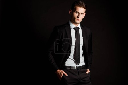 Photo for Handsome businessman in formal wear standing with hands in pockets isolated on black - Royalty Free Image