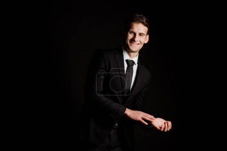 Photo for Happy businessman in suit smiling isolated on black - Royalty Free Image