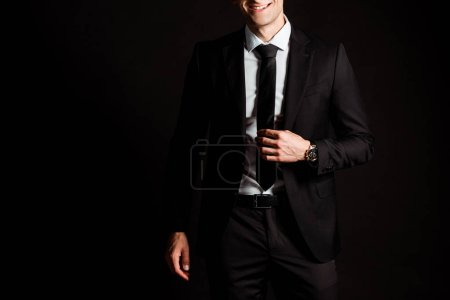 cropped view of happy businessman touching tie isolated on black