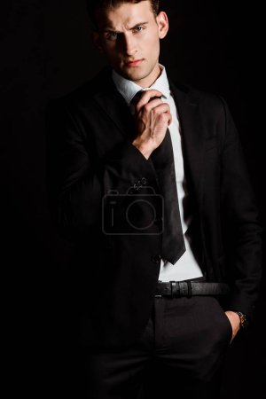 Photo for Handsome businessman touching tie and standing with hand in pocket isolated on black - Royalty Free Image